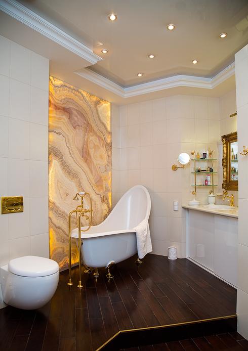 Ванная комната поражает своим великолепием: здесь панно из оникса и позолоченная фурнитура. Хотя, по словам хозяйки, сейчас она бы выбрала более лаконичный стиль